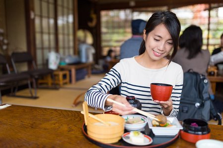 Woman having japanese meal inside a restaurant