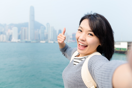 Woman taking photo her selfie in Victoria Harbor of Hong Kong
