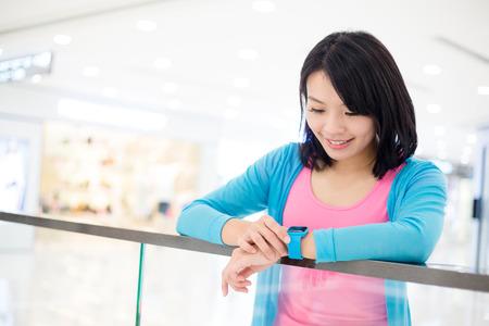 Woman using smart watch inside shopping mall Stock Photo