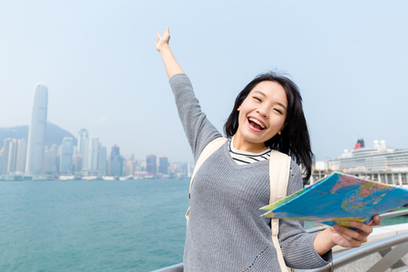 Thrilled woman holding a map and raised her hand Stock Photo