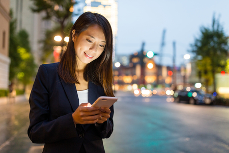 Businesswoman looking on cellphone in Tokyo city
