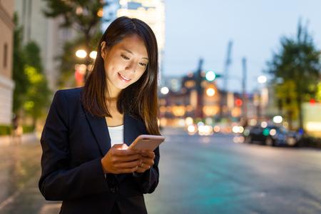 Onderneemster die op cellphone in de stad van Tokyo kijken