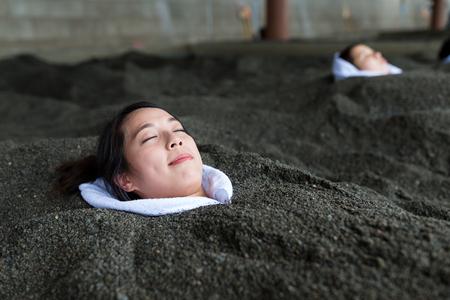 Woman enjoy hot sand bath