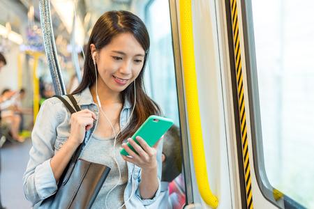 Vrouw luistert naar het liedje op de telefoon en neemt de trein in Hong Kong