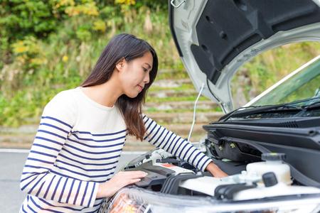 Vrouw die een motor van een auto probeert te herstellen