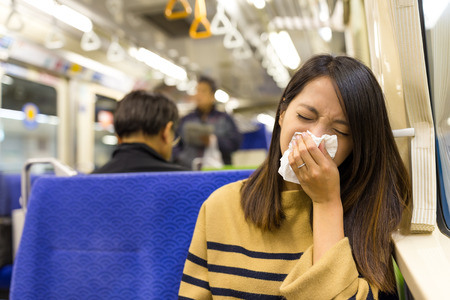 Young Woman sneezing on train