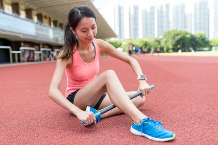 Sport woman using roller stick on legs