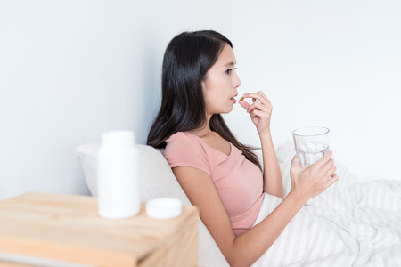 sleeping pills: Woman taking medicine and holding glass of water on bed
