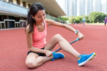 Sport woman using roller stick on legs in sport stadium