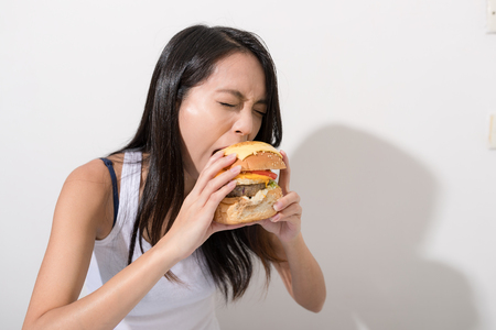 Woman eating burger over white background