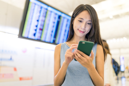 Woman checking time table on mobile phone in airport