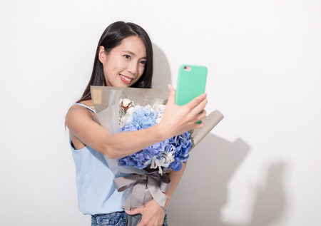 Woman holding bouquet of flower and taking selfie with mobile phone photo