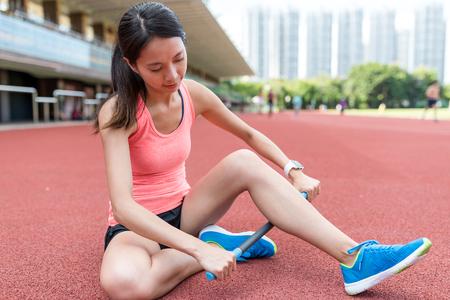 athletic wear: Sport woman using roller stick in stadium