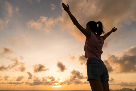 Silhouette of woman raising hand up under sunset Stock Photo