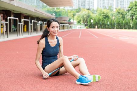 Asian Woman using roller massage stick in sport stadium