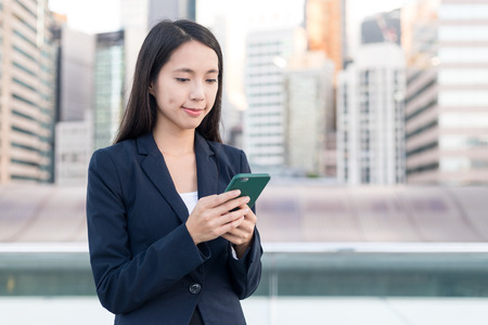 Business woman working on cellphone at outdoor Stock Photo