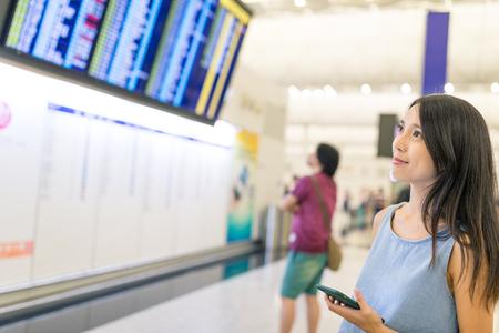 Vrouw die vluchtprogramma met cellphone en vertoningsraad controleert Stockfoto - 84674796