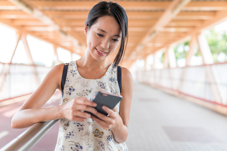 Woman looking at smart phone in the foot bridge