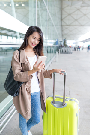 Woman using cellphone and luggage at airport
