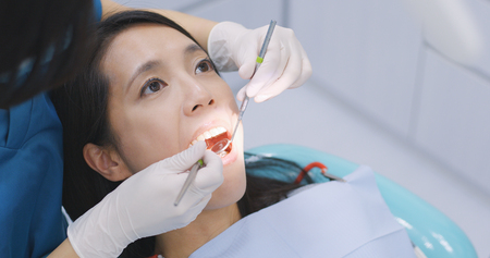 Woman undergo check up of tooth in dental clinic 免版税图像 - 96088245