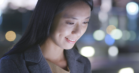 Asian Woman looks at mobile phone in city