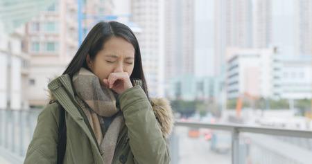 Woman sneezing at outdoor  Foto de archivo