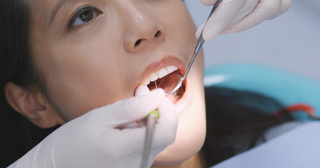Asian Woman undergo check up of tooth in dental clinic