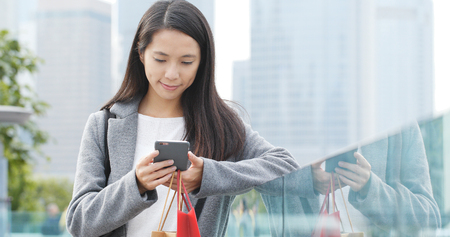 Woman look at mobile phone and holding shopping at outdoor  Banque d'images