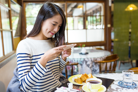 Woman taking photo on her breakfast in cafe Stock Photo