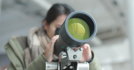 Woman looking through telescope to observe the bird habitat  Banque d'images