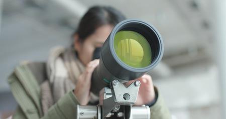 Woman looking through telescope to observe the bird habitat  Standard-Bild