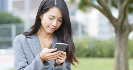 Business woman look at mobile phone in city