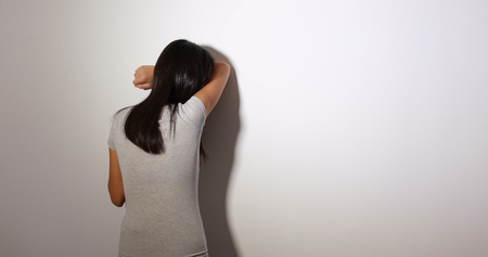Woman feeling upset and standing against the wall