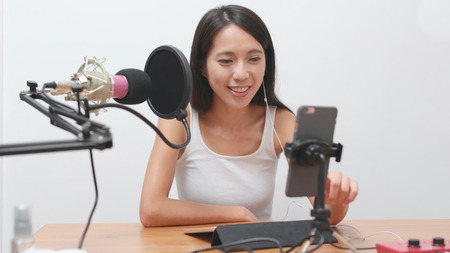 Beautiful woman having live stream on cellphone at home