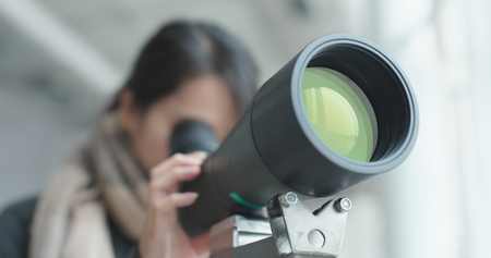 Woman looking though the telescope  Stockfoto