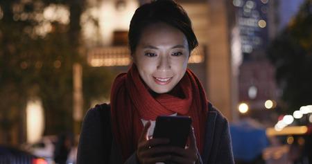 Femme regarder téléphone mobile dans la ville la nuit Banque d'images - 96091517
