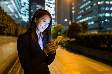 Businesswoman use of cellphone in Tokyo city