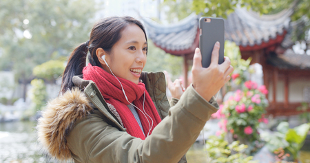 Woman making live stream on cellphone in chinese garden