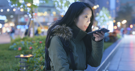 Woman sending audio message on cellphone at night  Banque d'images