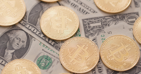 Pile of US dollar and bitcoin