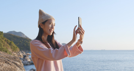 Woman taking video call on cellphone over seascape
