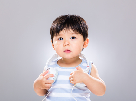 Little boy with music headphone on shoulder