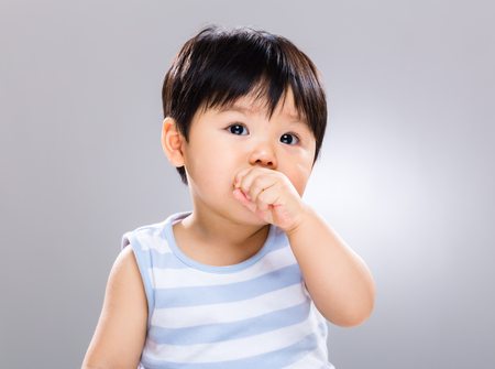 Asian baby son eating cookie Banco de Imagens