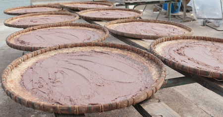 Shrimp paste being dried under the sun