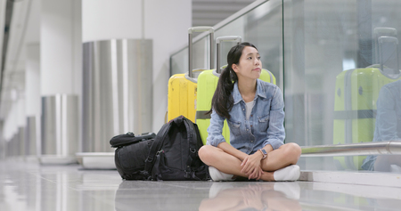 Woman wait so long for the flight transit at the airport carry with backpack and luggage