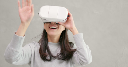 Woman playing VR device over gray background