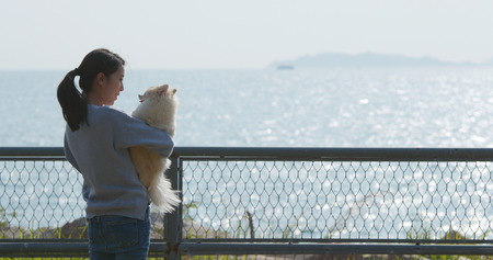 Woman hug with her dog and look at the sea Imagens