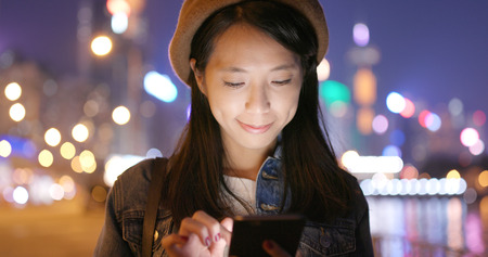 Woman look at smart phone in city at night