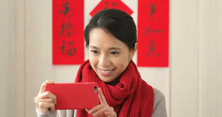 Woman taking family photo with cellphone during lunar new year period