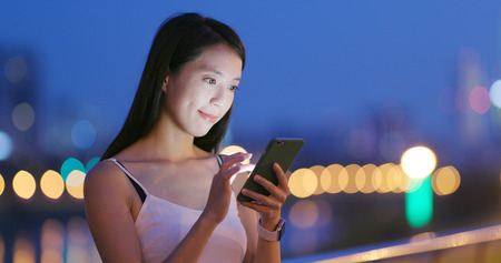 Asian woman use of mobile phone in the evening Foto de archivo